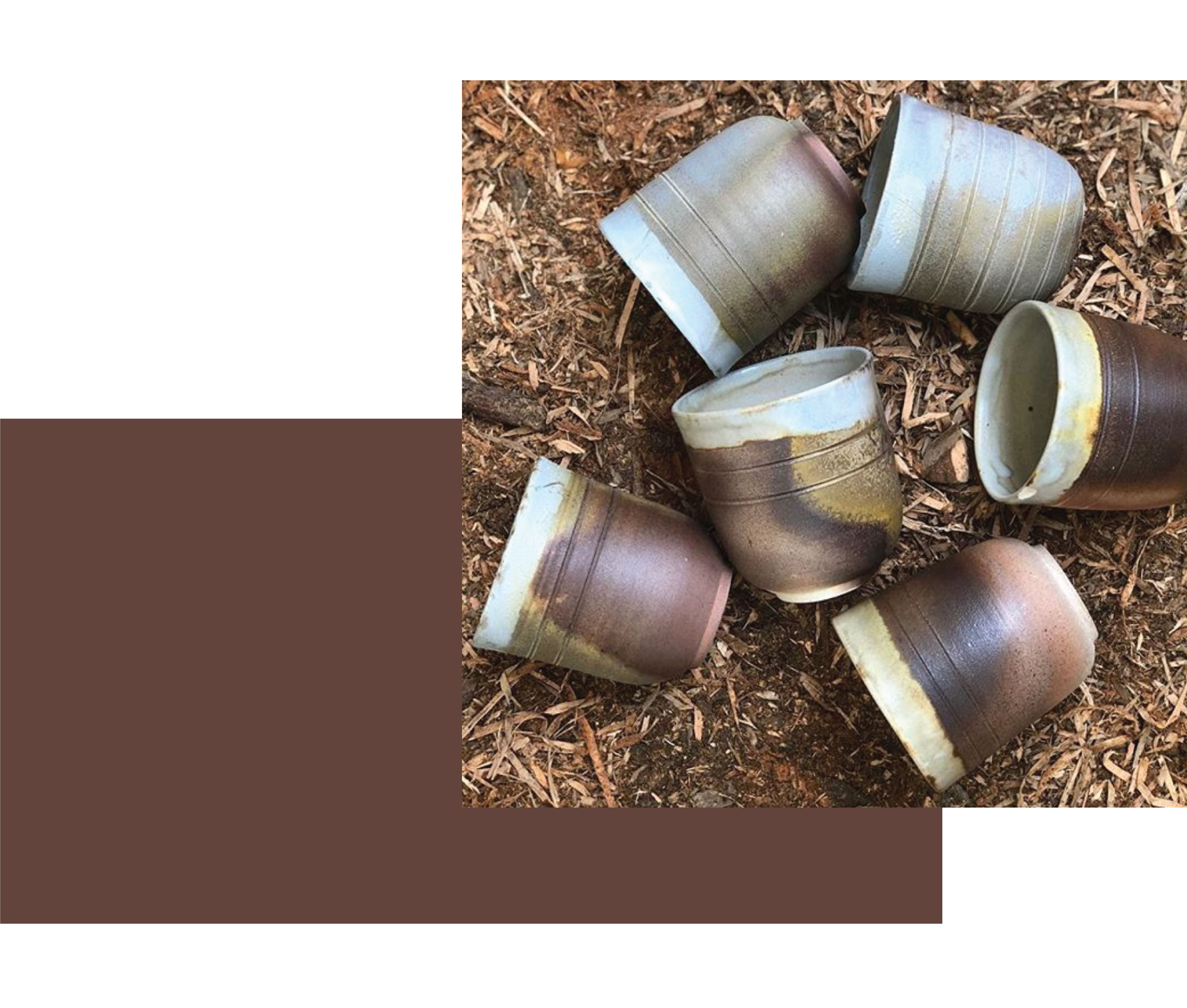 Pottery by New Zealand ceramist Galit Maxwell. 6 anagama woodfired ceramic tumblers in browns and blues, sitting on mulch bark textured background.