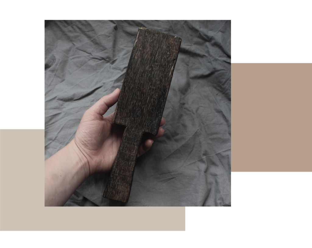 A clay paddle in a hand. The pottery tool is rectangular, wooden and about 30cm.