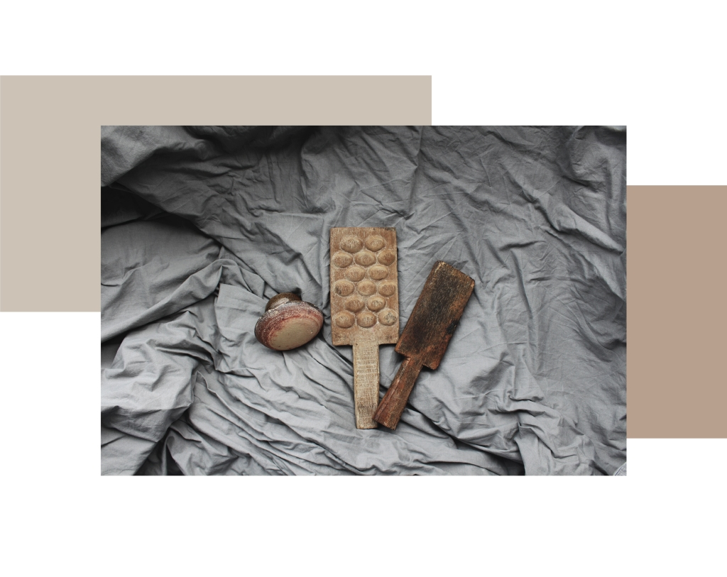 A ceramic pottery mushroom or anvil and two wooden pottery paddle tools.